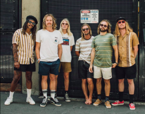 """Photo credit: Kane Lehanneur // The Sauce Northern Beaches funk lords Ocean Alley have taken out the #1 spot in triple j's Hottest 100 of 2018 with their groove-fuelled hit single 'Confidence', also placing #100, #16 and #10 for their standout tracks 'Happy Sad', Like a Version cover of 'Baby Come Back' and 'Knees' in the world's largest music poll. An undeniable fan favourite, 'Confidence' was certified gold in November, having moved over 35,000 units in 2018 and now surpassing 13 million streams since it was released last February. Three tracks are taken from the band's critically acclaimed second album Chiaroscuro, which debuted at #15 on the ARIA Album Chart and has gone on to clock up more than 35 million streams in its first 10 months - it's future classic status affirmed being voted #2 Album of the Year in triple j's end of year listener poll. Fresh following the announcement, the band exclaimed """"This is surreal. Thank you to our family, friends and all the team. To triple j and most importantly every single person that voted. Nothing is possible without your support."""" WATCH: Ocean Alley - 'Confidence' 2018 saw Ocean Alley solidify their position as one of Australia's most exciting bands, making their mark on the local and international touring circuit playing 96 shows across 10 countries and 60 cities, including selling 25,000 tickets across 15 sold out Australian shows. They were the 5th most played artist on triple j last year and have achieved the impressive feat of attaining over 900,000 monthly listeners on Spotify. Ocean Alley are back on the road next month, touring nationally with Tash Sultana through February and March before stopping into New Zealand for six shows in April. They'll return home for a performance at Byron Bay Bluesfest and then head back to the United States and Canada during the Australian winter months for an extensive run of dates. Ocean Alley – Baden Donegal (vocals), Angus Goodwin (guitar), Nic Blom (bass), Lach Galbraith (keys/"""