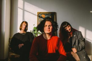"""Dot Dash Recordings and Remote Control Records are excited announce the signing of Melbourne's Obscura Hail. Today they release the first single 'Swear Jar' from their new EP Zero out Friday 25 October. Conceived on NSW's South Coast, and now buried alive somewhere in Melbourne, Obscura Hail (Sean Conran, Tamara Issa & Steven West) are sneaking into Melbourne's intimate spaces and filling strangers with relative truths. The somewhat serious themes of ontology, existentialism, love and loss are framed with sincerity by the lush, but gentle classical guitar work, and the motif of almost whispered, though richly layered vocal harmonies. The video for 'Swear Jar' was premiered via The Music Network this morning. Conran says of the video: """"Swear Jar is about the dumb stuff we fight about in the heat of the moment, and having the patience to find out what the other person really means without judging them on the language they used initially, on the premise that hindsight is the mother of foresight. For the clip we talked shop with the superb Mike Ridley and Nick McKK, and despite having a short timeline, we figured we'd act out a conflict in supernatural circumstances, initiated by playing a cursed board game; It's jumanji, but cloaked with the naive optimism of 'Bill and Ted'. That way the lesson isn't fear, it's that life is cool and totally heinous, and friendship is the best or whatever. I'm just glad we could tie in my surplus of teeth into the concept really."""" A commitment to their craft has culminated in Conran consistently delivering fresh compositions, drip fed weekly via his Patreon page, nearing its 160th volume. The last record, Pallbearer was self-produced and warmly received, now Obscura Hail can be found experimenting with more diverse live instrumentation to reflect the ever thickening arrangements in preparation for their newest release; Zero. Carrying a stark beauty, minimalist in nature but impressive in impact, the EP reflects the hands of Sun Kil Moon"""